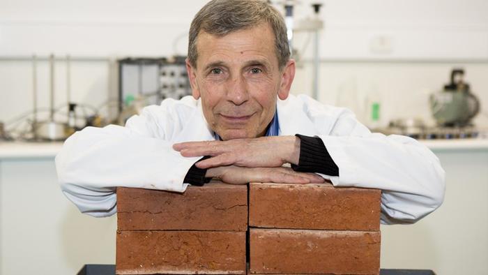 scientist leaning on bricks