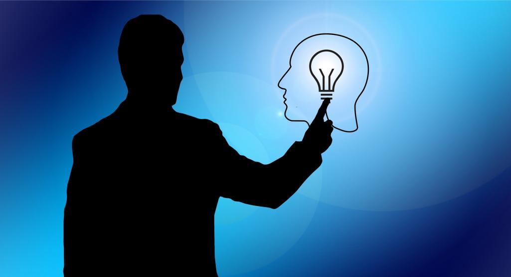 silhoette of man holding light bulb